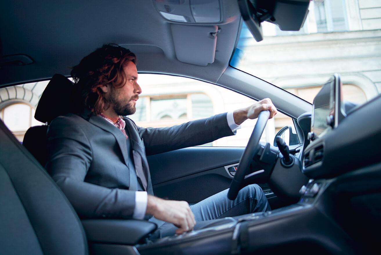 Un hombre sentado en el asiento del piloto de un vehículo Hyundai