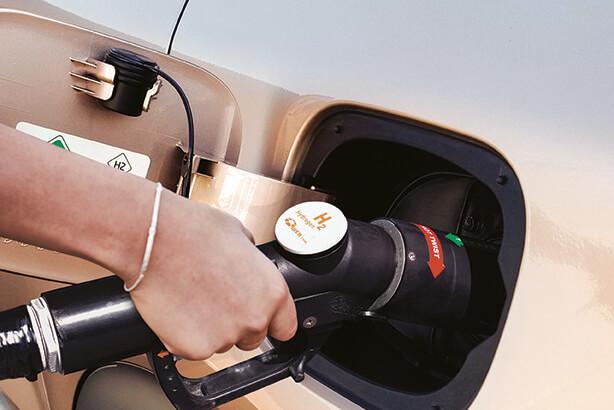Mujer cargando la batería de un coche eléctrico Hyundai